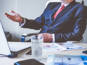 Image of man in blue business suit sitting at desk with hand open on Tips To Writing A Business Brochure Creative Copywriting & Content Solutions website