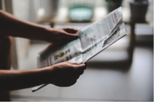 Image of two arms holding up newspaper on blog at Creative Copywriting & Content Solutions